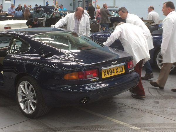 Men polishing an Aston Martin DB7 in a showroom